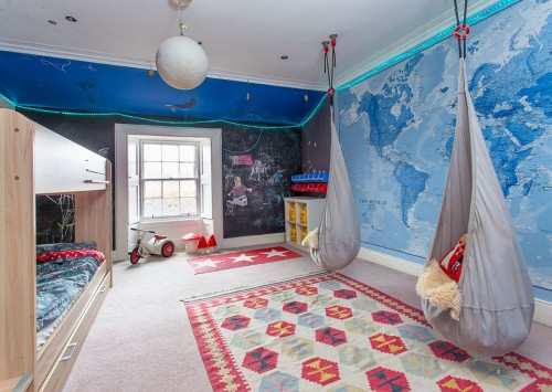 Boy's bedroom with Map of the World wallpaper on one wall